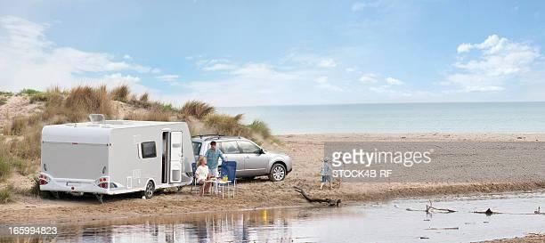 Family with caravan on the beach