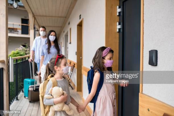 family with children and face masks outdoors by hotel in summer, holiday concept. - vacations stock pictures, royalty-free photos & images