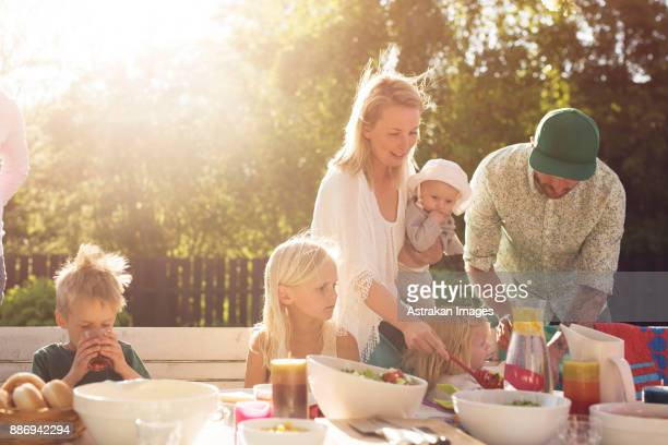 Family with children (2-3 months, 2-3, 4-5, 8-9) at picnic table