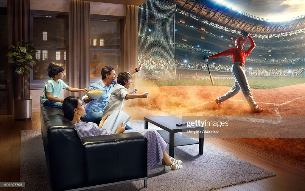 Family With Children Cheering And Watching Baseball Game On TV Stock Photo
