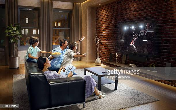 family with children cheering and watching basketball game on tv - family watching tv stock pictures, royalty-free photos & images