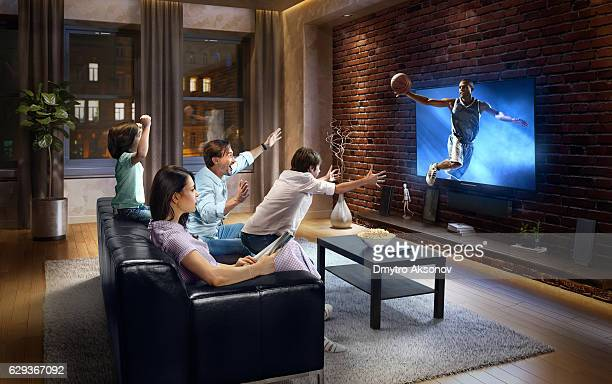 Family with children cheering and watching Basketball game on TV