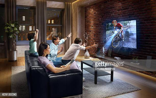 Family with children cheering and watching Cycle race on TV