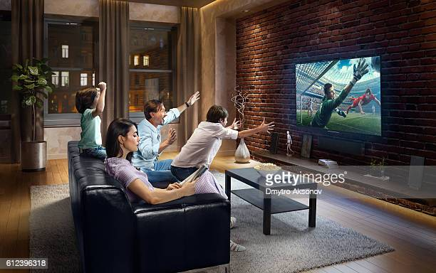 Family with children cheering and watching soccer game on TV