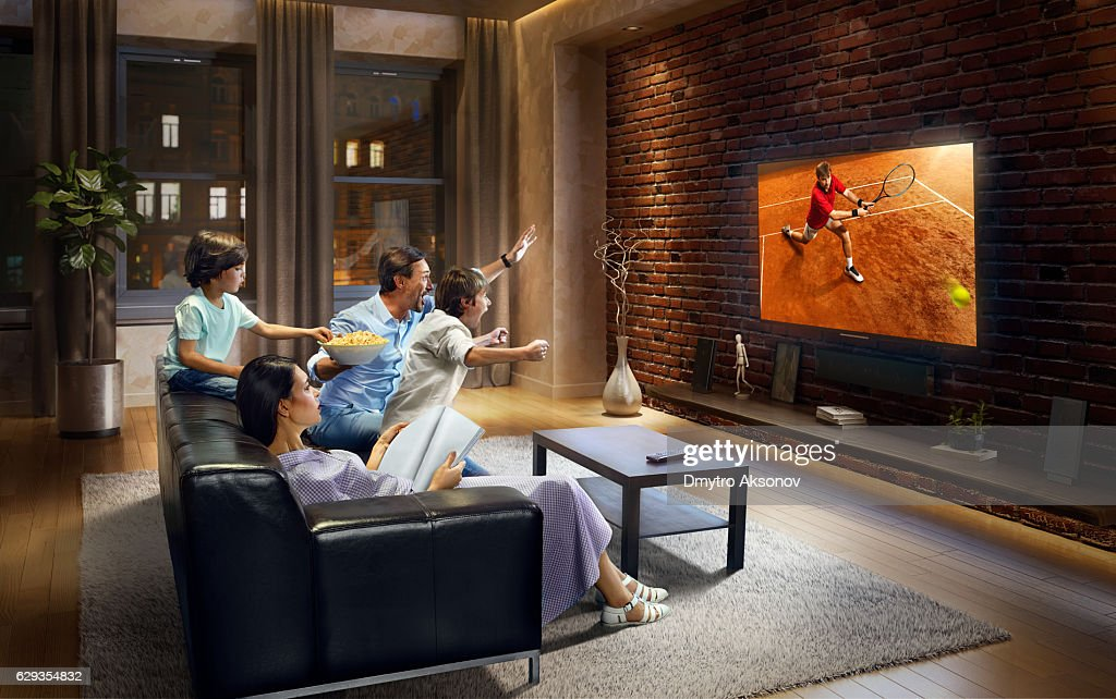 Family with children cheering and watching Tennis game on TV : Stock Photo