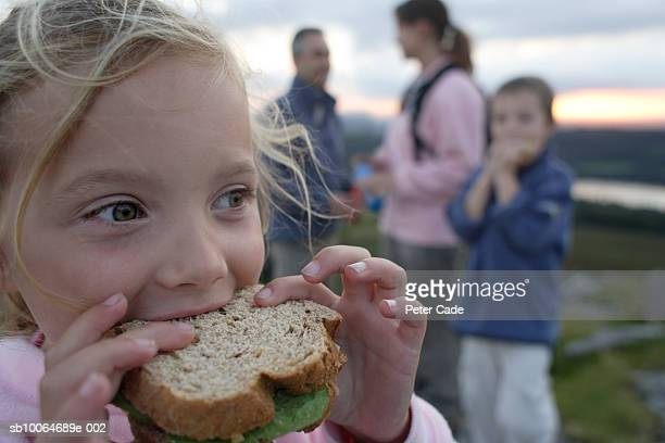 Family with children (6-8) eating sandwiches on moors, focus on girl in foreground