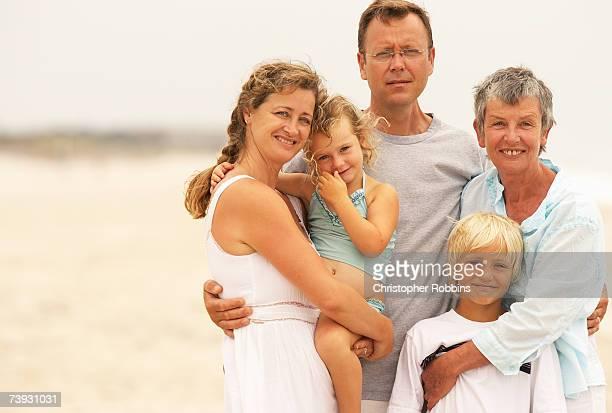 family with children (3-9) on beach, three quarter length - three quarter length ストックフォトと画像