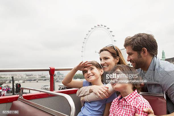 Family with children (10-11) on tour bus with view of London Eye and River Thames in background, London, England, UK