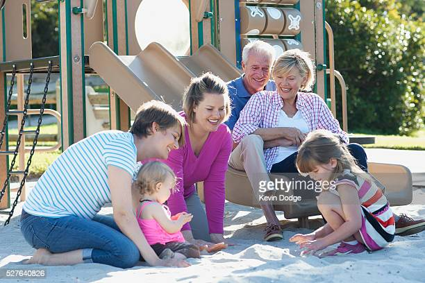 Family with children (12-23 months, 4-5years) playing in park