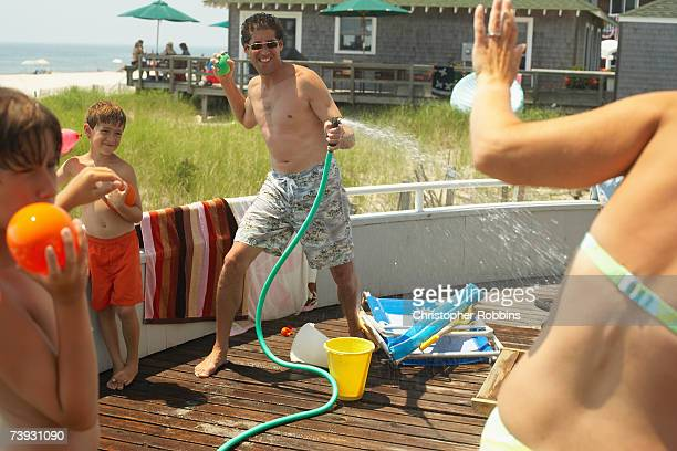 Family with children (8-11) playing with hose on decking