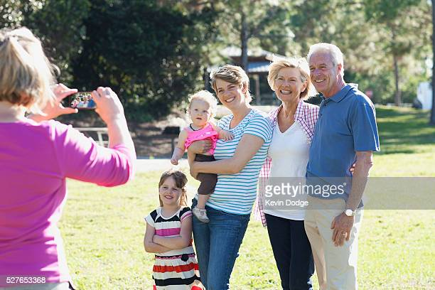 family with children (12-23 months, 4-5 years) taking photos in park - 55 59 years stock pictures, royalty-free photos & images