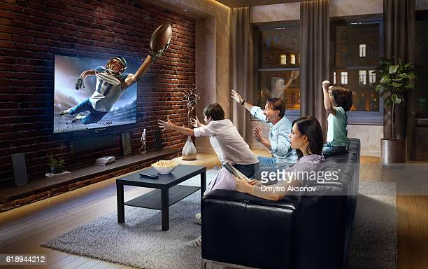 family with children watching american football game on tv - kunst kultur und unterhaltung fotos stock-fotos und bilder