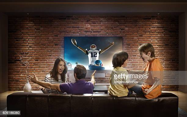 family with children watching american football game on tv - family watching tv stock pictures, royalty-free photos & images