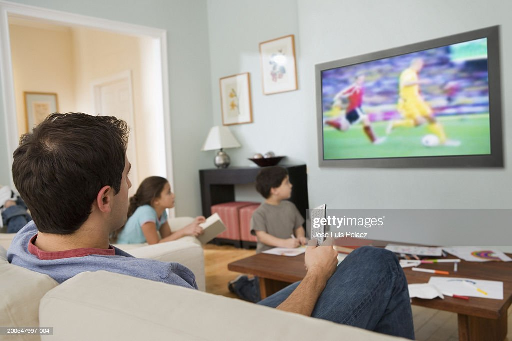 family with children watching flat screen tv in living room stock rh gettyimages com flat screen tv in small living room flat screen tv placement in living room