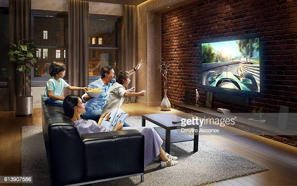 family with children watching sports car race on tv - auto racing photos stock pictures, royalty-free photos & images