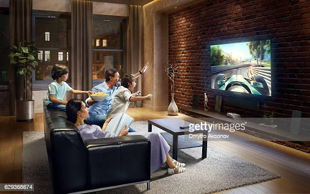Family with children watching Sports Car Race on TV
