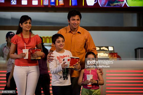 Family with cola and popcorn