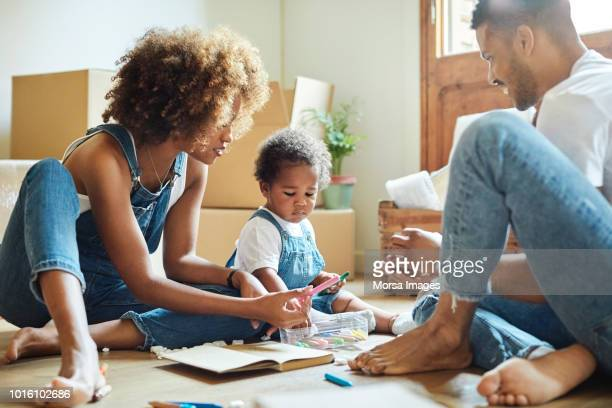 family with colored pencils in new house - unpacking stock pictures, royalty-free photos & images