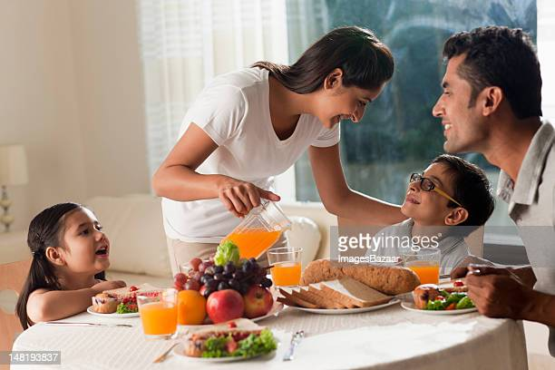 family with daughter and son (6-7) having breakfast - indian subcontinent ethnicity stock pictures, royalty-free photos & images