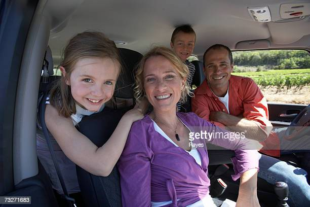 Family with daughter (7-9) and son (6-8) smiling in car