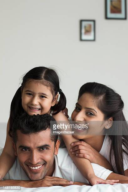 Family with daughter (6-7) relaxing in bed