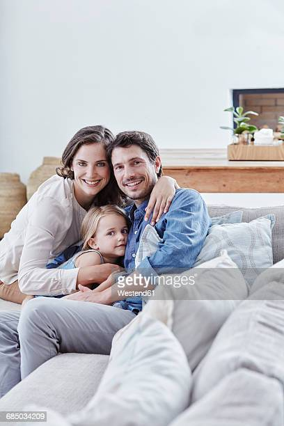 Family with daughter relaxing on couch