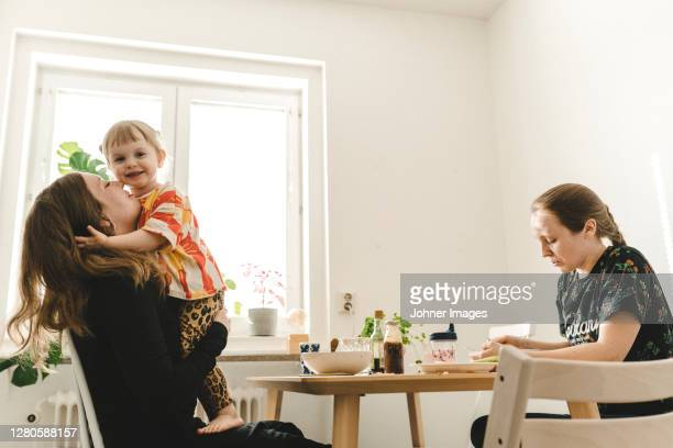 family with daughter sitting at table - relationship stockfoto's en -beelden