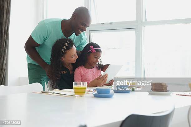 Family with digital tablet at breakfast table