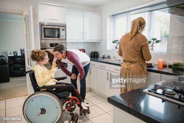 family with disabled daughter in the kitchen - als stock photos and pictures