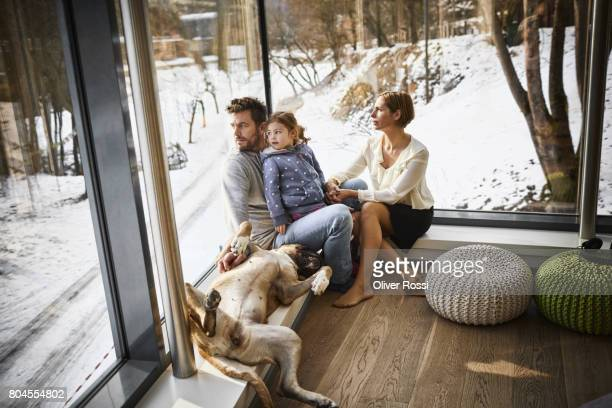 Family with dog at home sitting at the window