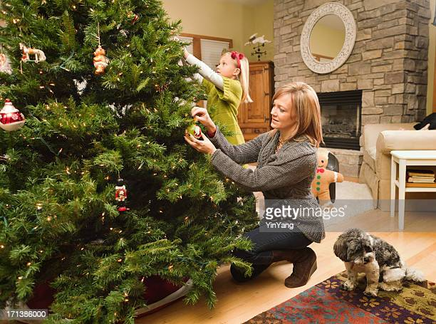 Family with dog decorating Christmas tree