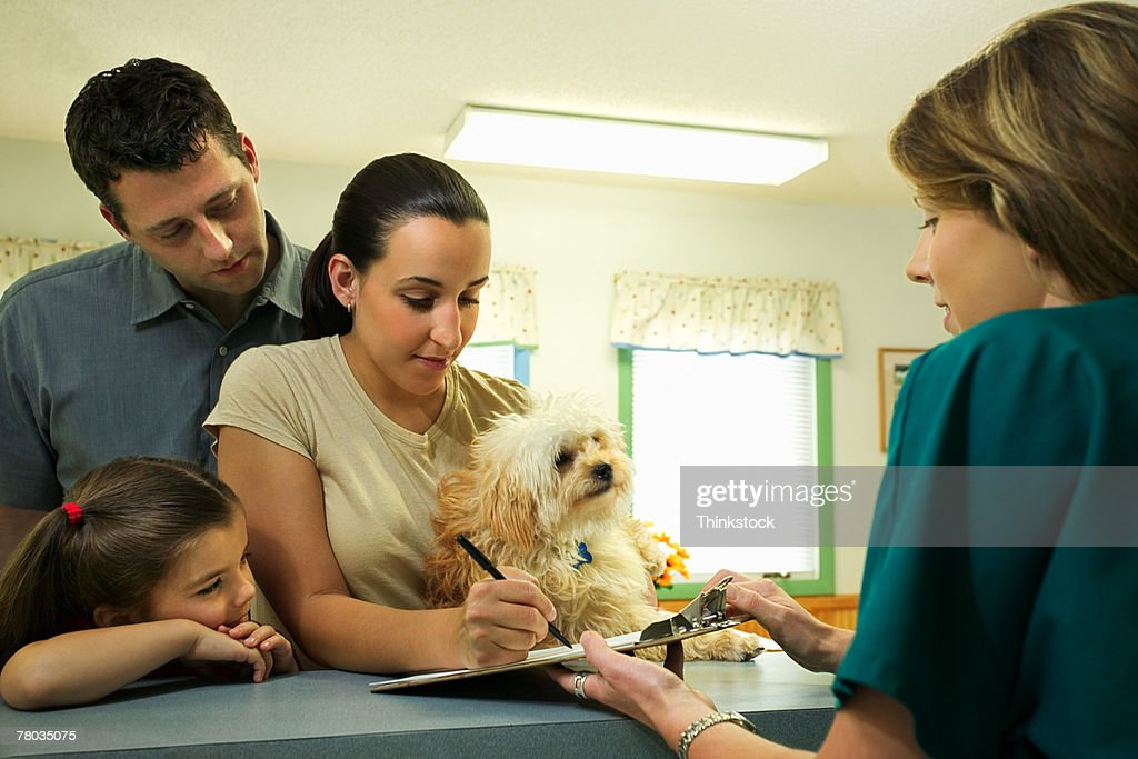 Family with dog filling out paperwork at vet clinic : Stock Photo