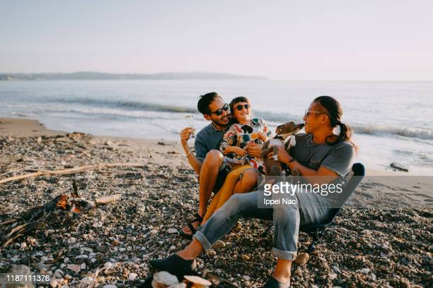 family with dog having fun at beach camping site - recreational pursuit stock pictures, royalty-free photos & images
