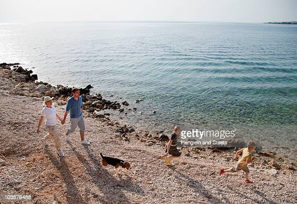 Family with dog running at the beach