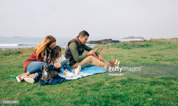 Family with dog sitting on blanket at the coast using wireless devices
