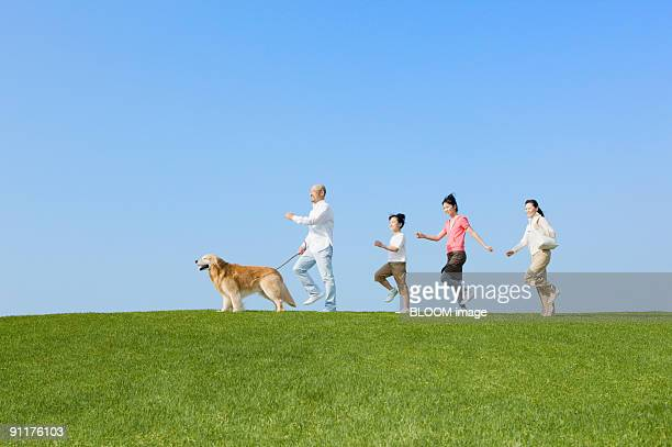 Family with dog walking in park