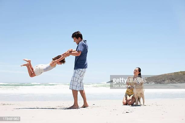 Familie mit Hund zu Fuß am Strand
