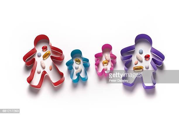 family with dose of vitamins in cookie cutters - dose stock pictures, royalty-free photos & images