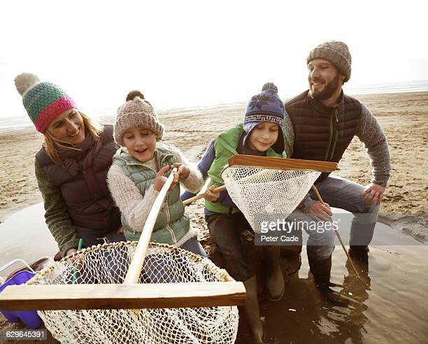 Family with fishing nets on beach in winter