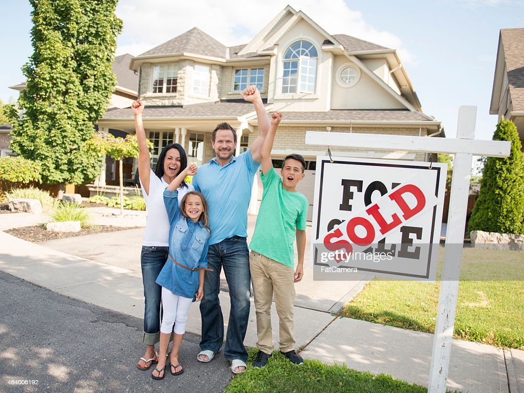 "Family with ""For Sale, Sold"" real estate sign : Stock Photo"
