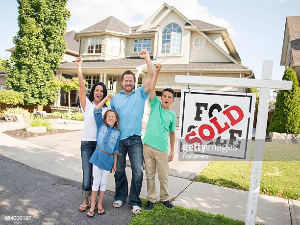 Family with 'For Sale, Sold' real estate sign