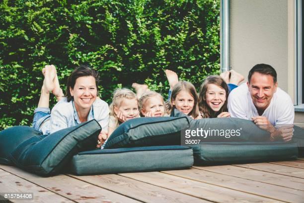 Familie mit vier Kindern liegen auf der Terrasse