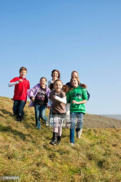 Family with four kids running over meadow