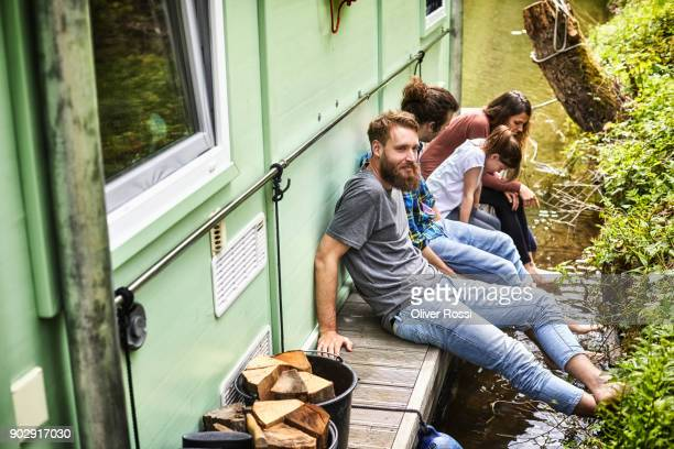 family with friend relaxing on a houseboat - houseboat stock pictures, royalty-free photos & images