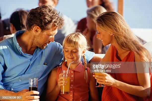 family with girl (8-9 years) drinking soft drinks, waist up - 30 39 years stock-fotos und bilder
