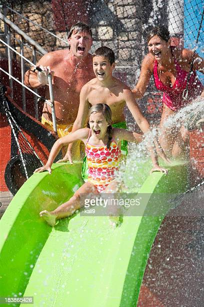 Family with girl going down slide at water park