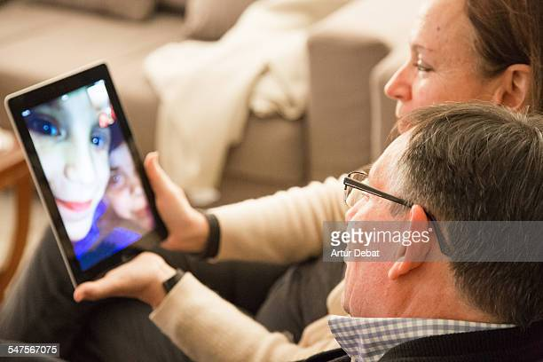 family with grandparents doing facetime with tablet computer. - voip stockfoto's en -beelden