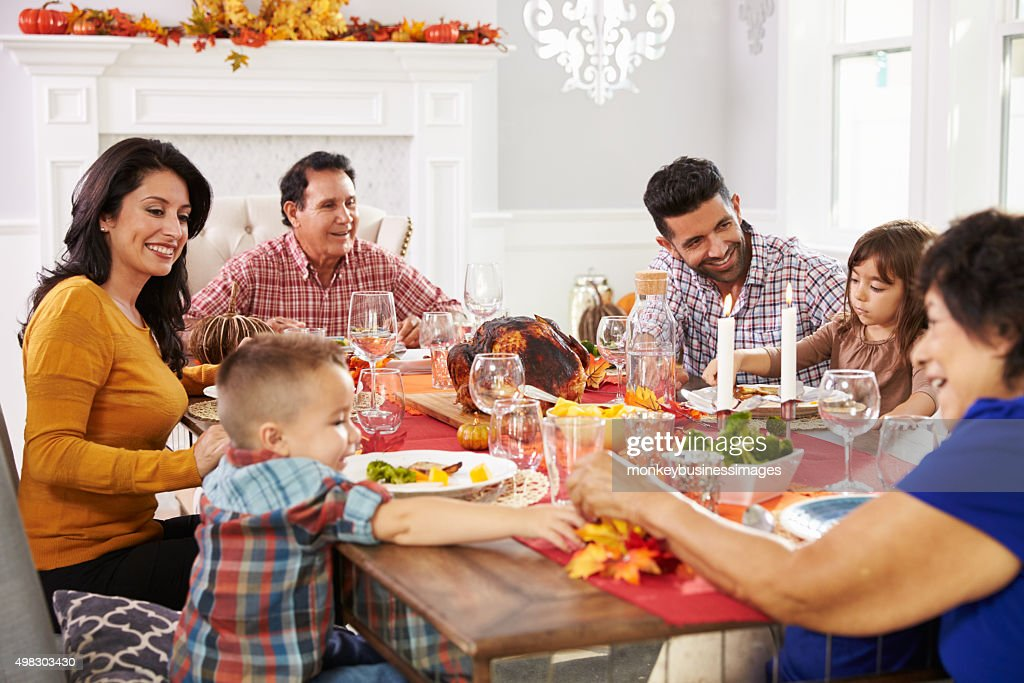 Family With Grandparents Enjoying Thanksgiving Meal At Table : Stock Photo