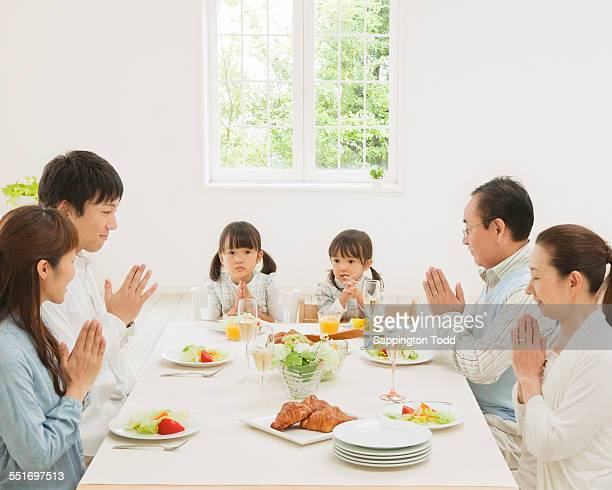 Family With Hands Joined Before Meal