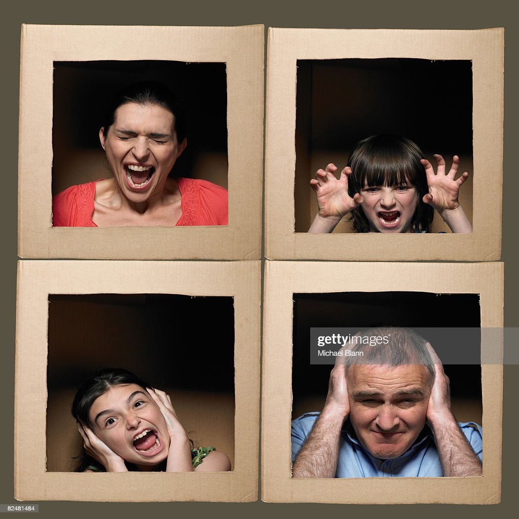 Family with heads in boxes pulling faces : Stock Photo